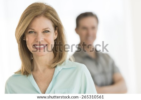 Portrait of beautiful woman smiling with man standing in background at home - stock photo
