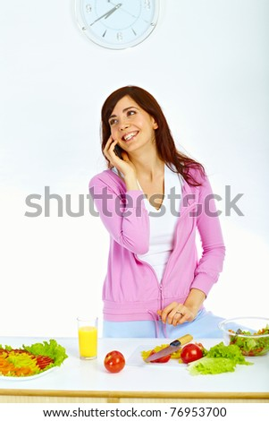 Portrait of beautiful woman standing in kitchen and talking on the mobile phone - stock photo