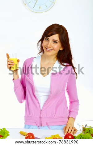 Portrait of beautiful woman standing in the kitchen with glass of orange juice and smiling - stock photo