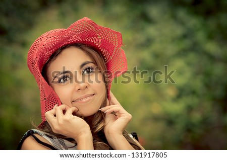 Portrait of beautiful woman standing in the middle of the forrest and holding her hat down with smile - stock photo