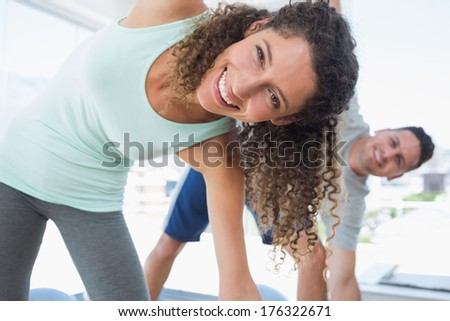 Portrait of beautiful woman stretching in exercise room - stock photo