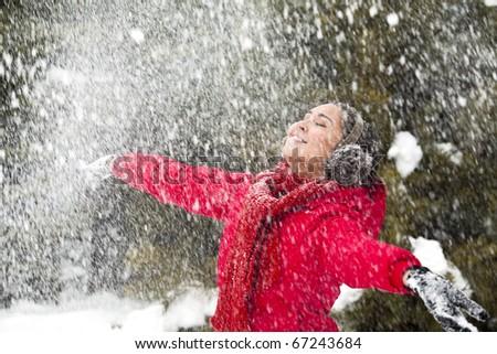 Portrait of beautiful woman taking pleasure on snowy winter day - stock photo