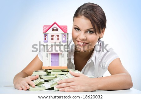 Portrait of beautiful woman touching heap of money with toy house on its top