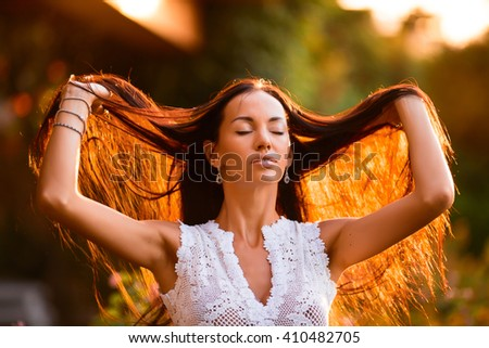 portrait of beautiful woman touching her hairs in the sunset on a background - stock photo