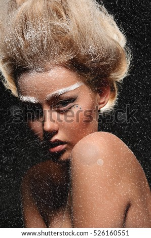 Portrait of beautiful woman under falling snow on dark background