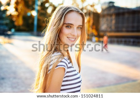 Portrait of beautiful woman walking in the city - stock photo