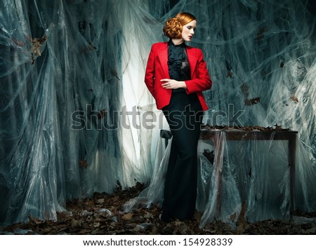 portrait of beautiful woman wearing red jacket and long skirt against autumn decoration - stock photo