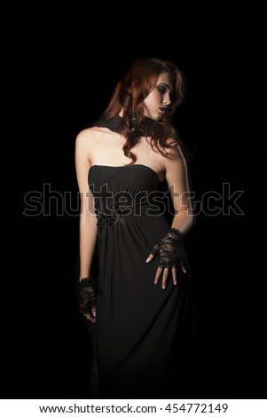 Portrait of beautiful woman wearing strapless black dress, black lace gloves and black scarf