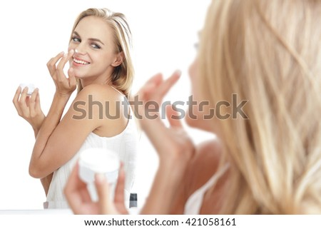 portrait of beautiful woman while  applying some facial cream on her nose isolated on white background - stock photo