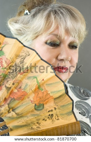 portrait of beautiful woman with a fan - stock photo
