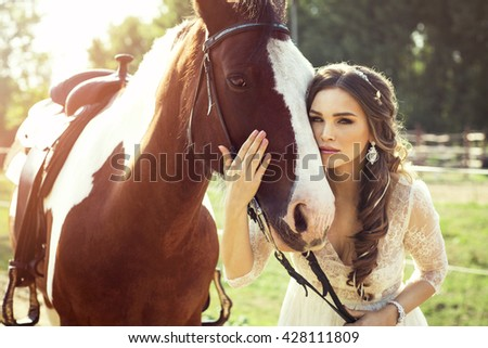 Portrait of beautiful woman with a horse. Beautiful bride wear wedding dress and hugging a horse - stock photo