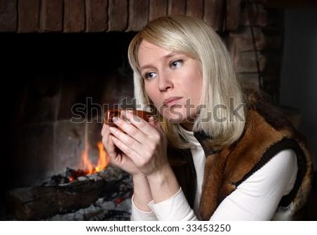 Portrait of beautiful woman with a mug near a fireplace - stock photo