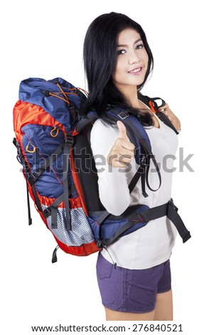 Portrait of beautiful woman with backpack for hiking, standing in the studio while showing thumb up on the camera - stock photo