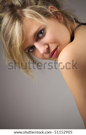 Portrait of beautiful woman with bare shoulder against dark background