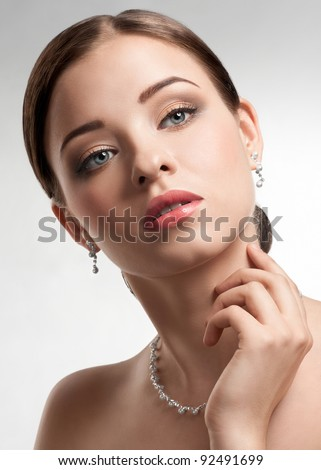 Portrait of beautiful woman with beautiful make-up and hairstyle. Elegant woman with pearl jewelry - stock photo
