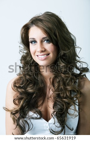 Portrait of beautiful woman with blue eyes and long curly hair - stock photo