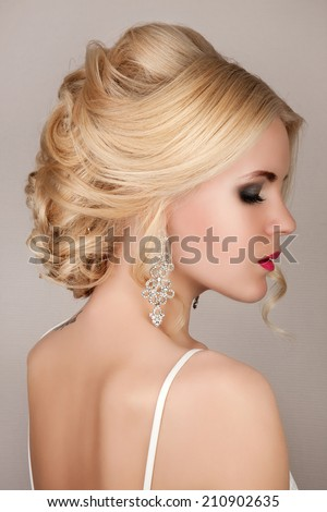 Portrait of beautiful woman with bridal makeup, hairstyle and jewelry - earrings, wedding style