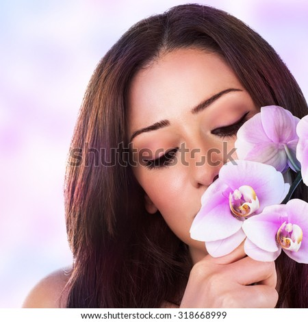 Portrait of beautiful woman with closed eyes of pleasure enjoying nice sweet smell of pink fresh orchid flower over blur background, luxury spa salon - stock photo
