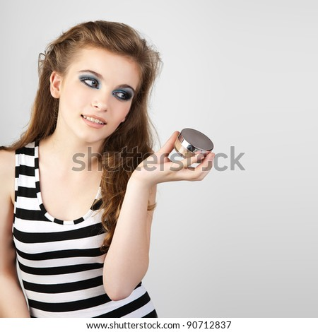 Portrait of beautiful woman with cream in her hands - stock photo