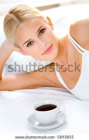 Portrait of beautiful woman with cup on bed at bedroom - stock photo