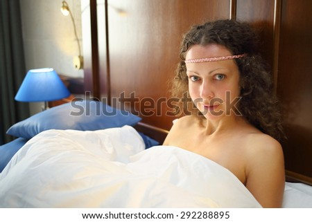 Portrait of beautiful woman with curly hair under a white blanket in the bed - stock photo