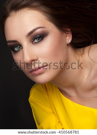 Portrait of beautiful woman with evening make-up in yellow dress - stock photo