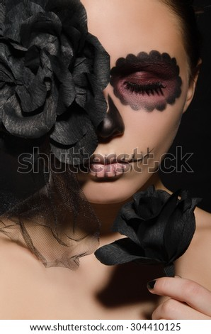 portrait of beautiful woman with face art and flower studio shot - stock photo