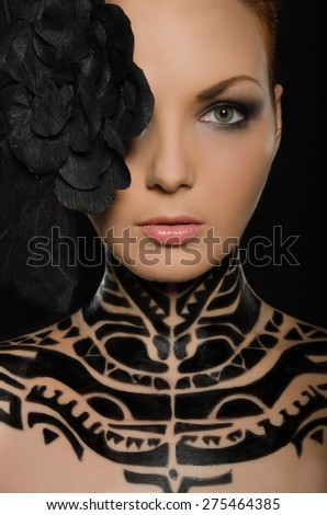 Portrait of beautiful woman with flower and black body art on black background - stock photo