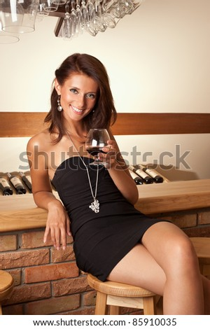Portrait of beautiful woman with glass of cognac - stock photo