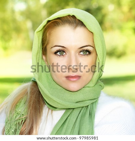 Portrait of beautiful woman with green scarf outdoors. - stock photo