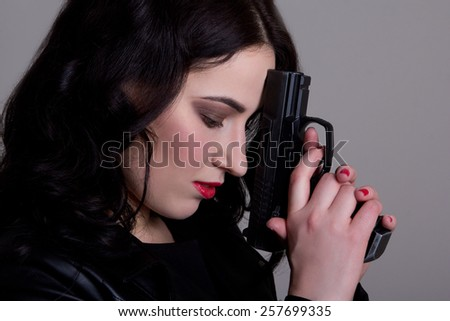 portrait of beautiful woman with gun over grey background - stock photo