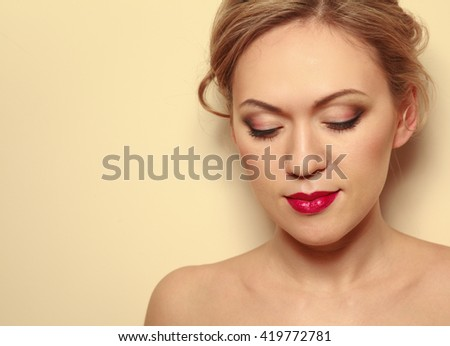 Portrait of beautiful woman with hairstyle and makeup looking down - stock photo