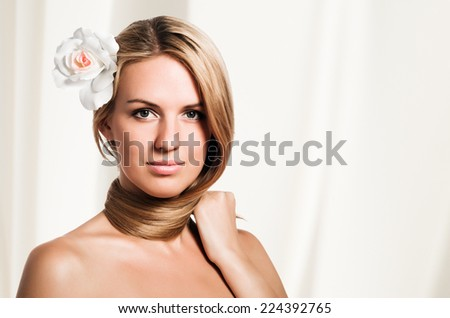 Portrait of beautiful woman with healthy skin with flower in her hair. - stock photo