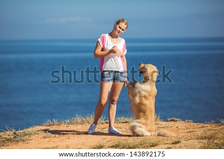 Portrait of beautiful woman with her retreiver dog playing near blue sea - stock photo