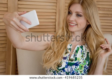 Portrait of beautiful woman with long blond hair making a selfie using a smart phone and smiling, sitting on armchair at home. - stock photo