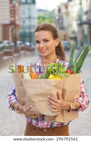 Portrait of beautiful woman with long red hair. Young woman posing with bags full of different fruits and vegetables. - stock photo