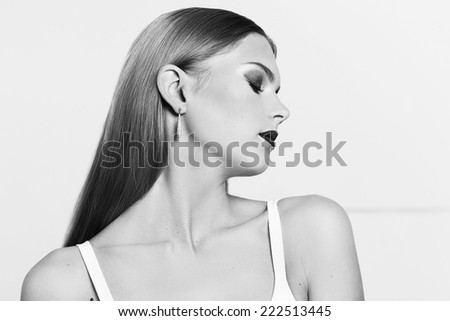 Portrait of beautiful woman with long straight shining hair on white background. Make up. Fashion portrait. Stylish woman. High fashion model. Black and white.
