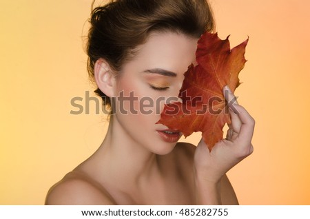 portrait of beautiful woman with maple autumn leaves on yellow background