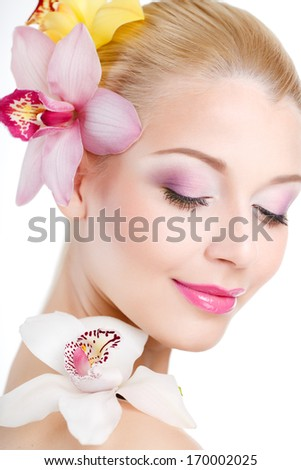 portrait of Beautiful woman With Orchid Flowers.Beautiful Model Woman Face. Perfect Skin. Professional Make-up.Makeup. Fashion Art - stock photo