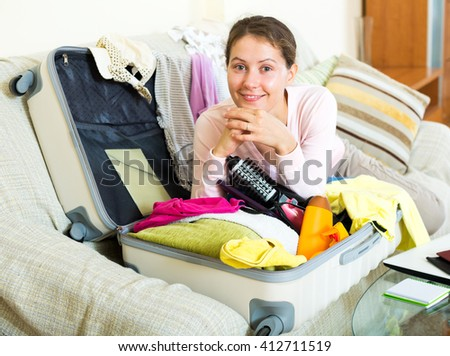 Portrait of beautiful woman with packed baggage and notes - stock photo