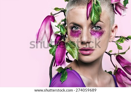 portrait of beautiful woman with pink glitter make-up and magnolia  - stock photo