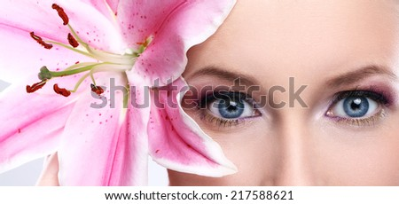 Portrait of beautiful woman with pink lily flower - stock photo
