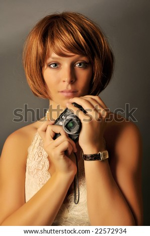 Portrait of beautiful woman with red hair holding compact camera.