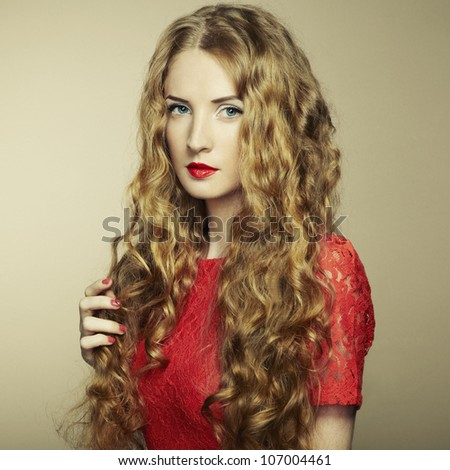 Portrait of beautiful woman with red hair in red dress. Fashion photo - stock photo