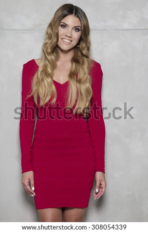 Portrait of beautiful woman with red lips and curly hair wearing dress - stock photo
