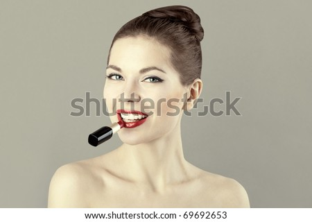Portrait of beautiful woman with red lipstick, doing makeup