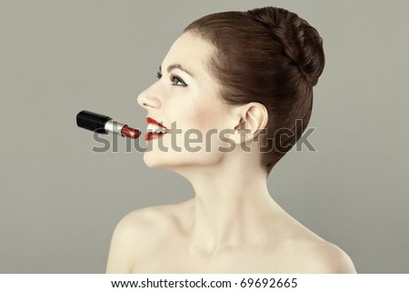 Portrait of beautiful woman with red lipstick, doing makeup - stock photo