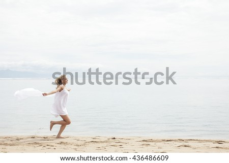 portrait of beautiful woman with scarf feeling free on the beach with copy space - stock photo