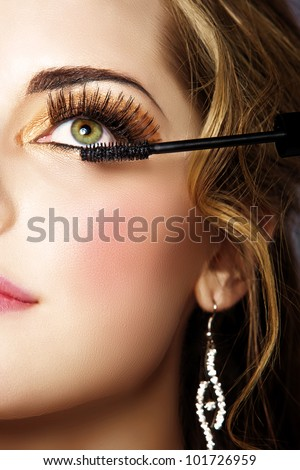 portrait of beautiful woman with smoky gold eyeshadow and long false eyelashes applying mascara with a wand - stock photo