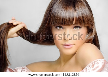 Portrait of beautiful woman with straight long hair on gray background - stock photo